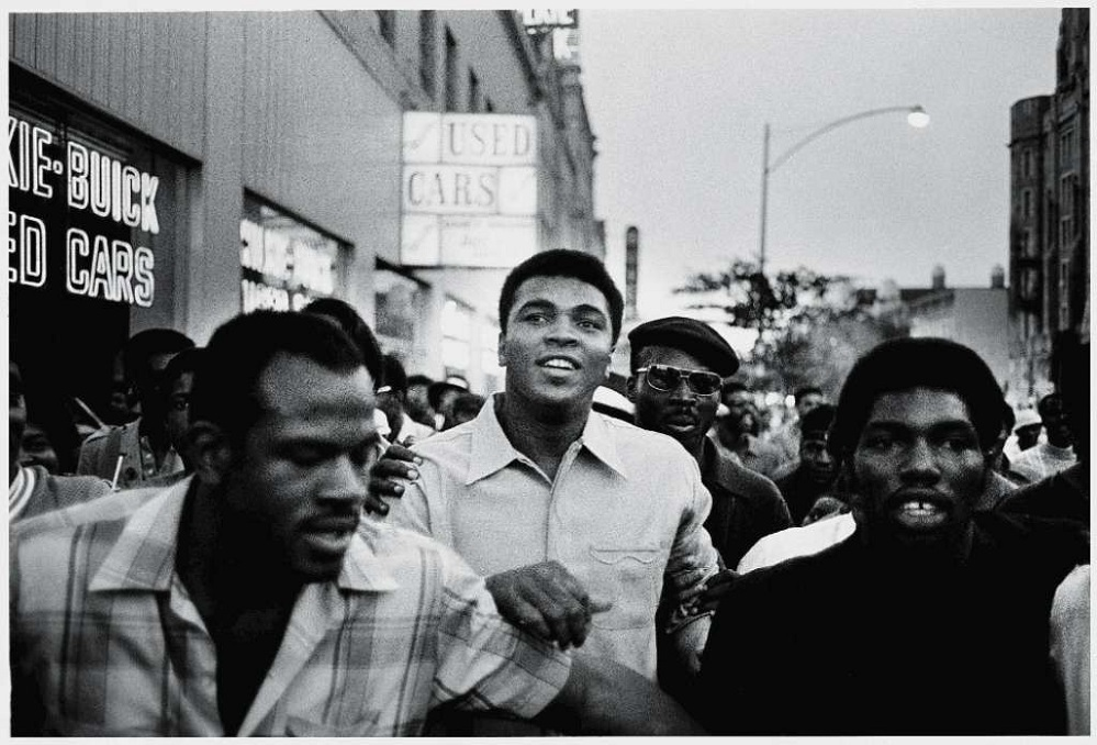 Muhammad Ali walks through the streets with members of the Black Panther