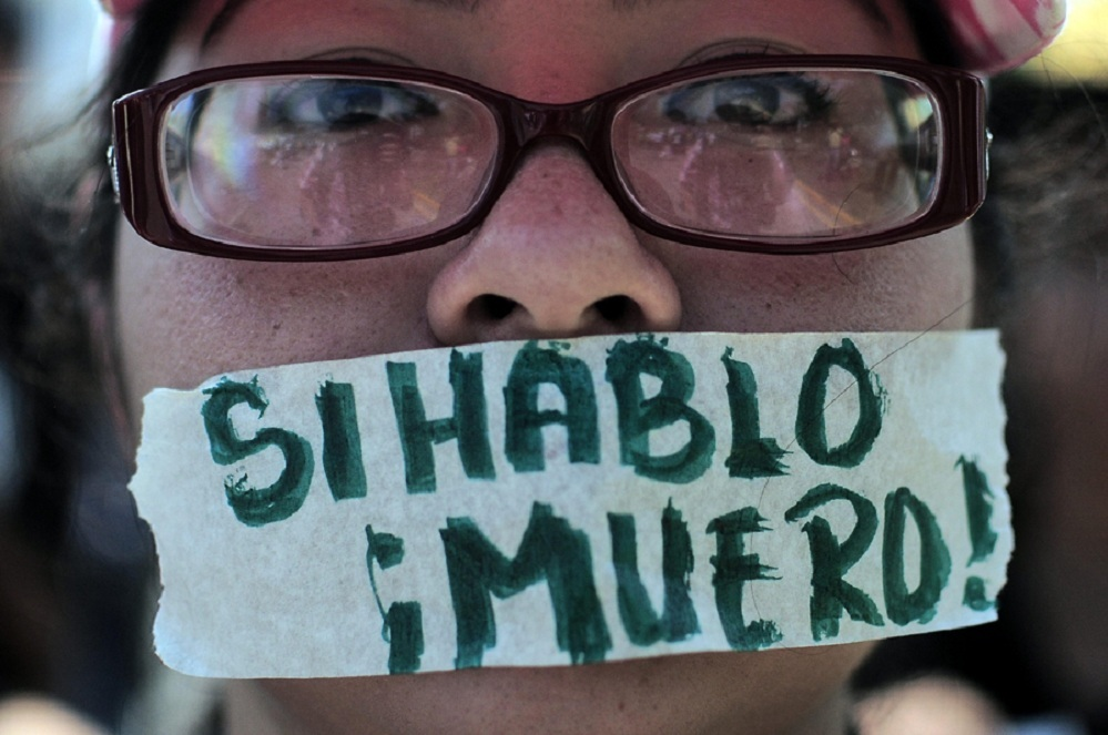 A protester denounces violence against journalists in Honduras Photo CNS