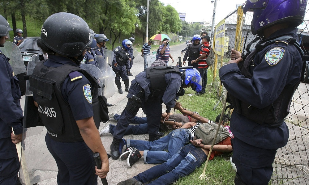 Honduras police agents detain campesino leaders in the Aguan Valley at a protest in the capital