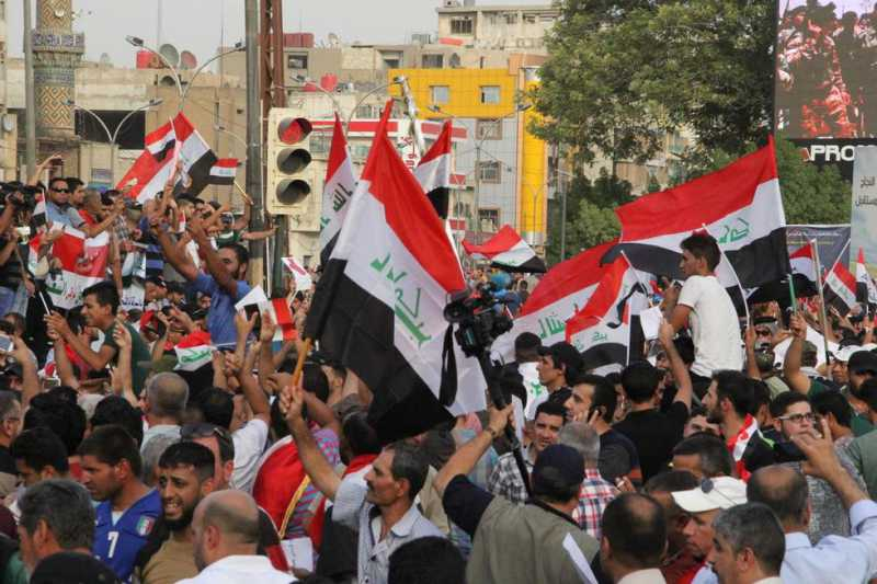 6fc618054f6443648d57f4c82Iraq_Thousands_of_Iraqi_demonstrators_hold_national_flags_as_they_gather_at_Tahrir_Square_to_protest_power_cuts_in_Baghdad_Iraq_on_August_7_2015_AA.jpg